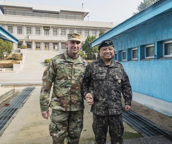 로버트 에이브람스 사령관과 박한기 합참의장이 10일 판문점 공동경비구역 군사분계선 위에서 손을 잡고 기념촬영하고 있다. [사진 주한미군]