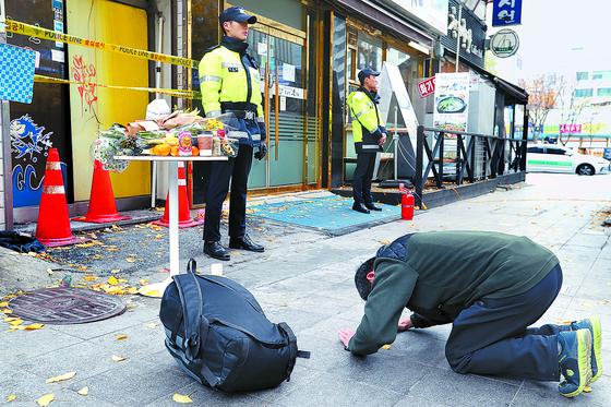 7명의 목숨을 앗아간 서울 종로 고시원 화재 현장에서 11일 한 시민이 추모 꽃과 음료수 등이 올려진 테이블을 향해 절하고 있다. 이날 희생자 중 5명의 장례가 국립중앙의료원 등에서 치러졌다. [장진영 기자]