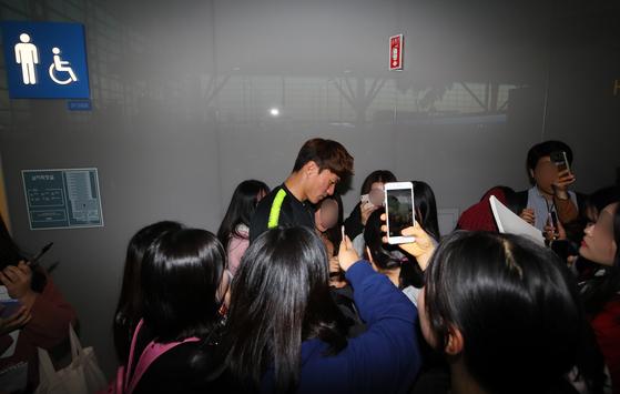 축구국가대표팀 공격수 황의조가 12일 인천공항에서 호주로 출국하기 전 모여든 팬들에게 사인해 주고 있다. [연합뉴스]