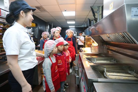 맥도날드 잠실DT점의 주방에서 소비자들이 튀김 제조 과정을 살펴보고 있다. [사진 한국맥도날드]