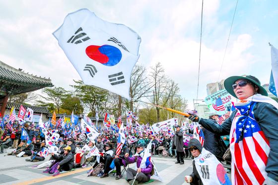 박근혜 전 대통령 지지자들이 덕수궁 앞에서 열린 태극기시민혁명운동본부 주최 태극기 혁명 국민 대회에서 태극기와 성조기를 흔들고 있다. [뉴스1]