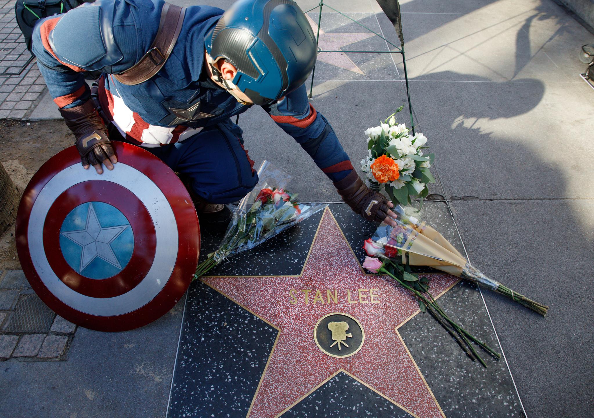 캡틴 아메리카 분장을 한 시민이 12일(현지시간) 스탠 리를 추모하 미국 할리우드 명예의 거리에 새겨진 그의 이름 앞에 헌화를 하고 있다. [EPA=연합뉴스]