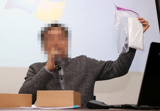 공익신고자 A씨가 13일 오후 서울 중구 세종대로 뉴스타파에서 기자간담회를 갖고 '양진호 한국미래기술 회장이 허위진술을 강요하며 돈봉투를 건냈다'며 비닐 봉투에 담긴 돈봉투를 들어보이고 있다. [뉴스1]
