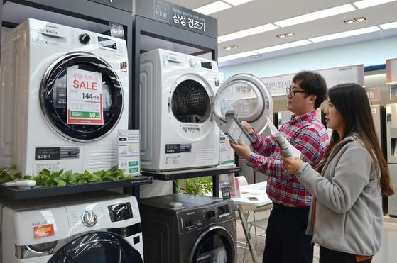 서울의 한 전자제품 양판점에서 소비자들이 의류건조기를 살펴보고 있다. 가전업계에 따르면 건조기 판매량은 봄가을의 미세먼지, 여름철 고온다습한 날씨, 아파트 주거 인테리어 변화 등의 영향으로 지난해 60만 대에서 올해 150만 대로 커질 전망이다. [사진 전자랜드]