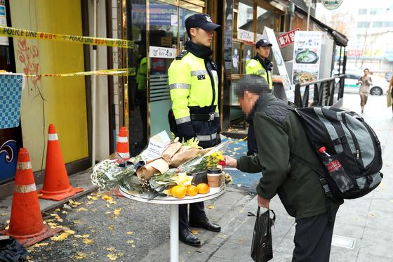 화재로 7명이 사망한 서울 종로구 국일고시원 앞에서 11일 한 시민이 추모 테이블에 음료수를 놓고 있다. [중앙포토]
