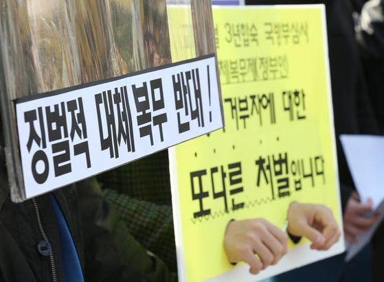 지난 5일 오전 서울 용산구 국방부 앞에서 열린 '정부의 양심적 병역거부 징벌적 대체복무제안 반대' 기자회견에서 병역 거부자 및 사회단체 회원들이 대체복무제안 수정을 촉구하는 손팻말을 들고 있다. [연합뉴스]