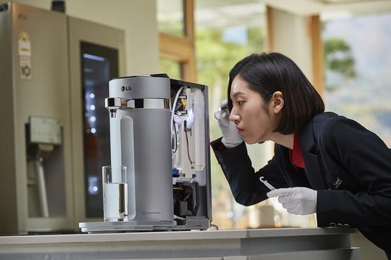 LG전자 렌털 제품 관리 직원인 헬스케어 매니저가 정수기를 점검하고 있다. [사진 LG전자]