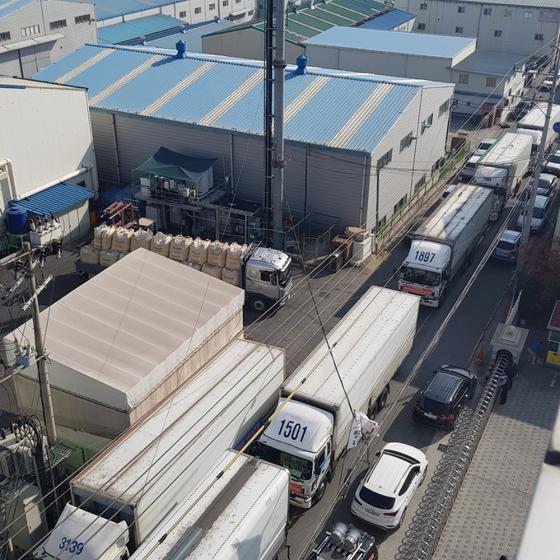 지난 5일 화물연대 울산지부 소속 기사들이 트럭으로 성우하이텍 공장 인근 도로를 가로막은 모습. [사진 국제신문]