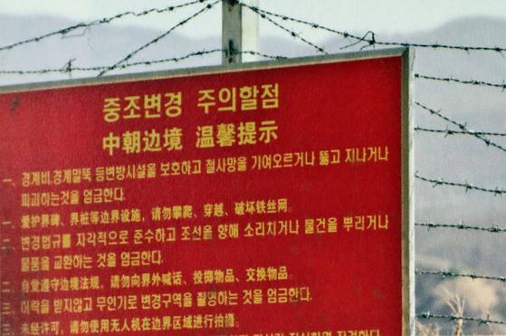 어른 키 두 배 높이 펜스 위로 끝없이 뻗은 가시철망에 경고문구가 적힌 표지판이 설치돼있다.[사진 강동완]