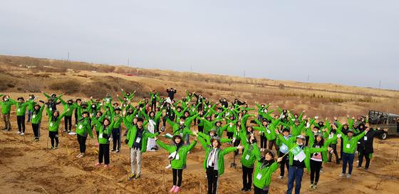 중국 쿠부치 사막에서 포플러를 심은 한중 녹색봉사단원들이 만세를 부르고 있다.