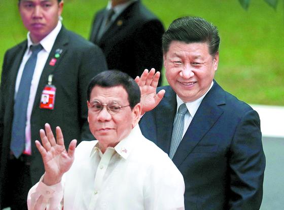 필리핀을 방문한 시진핑 중국 국가주석(오른쪽)이 20일(현지시간) 마닐라 마라카낭 궁에서 두테르테 필리핀 대통령과 함께 손을 흔들고 있다. [로이터=연합뉴스]