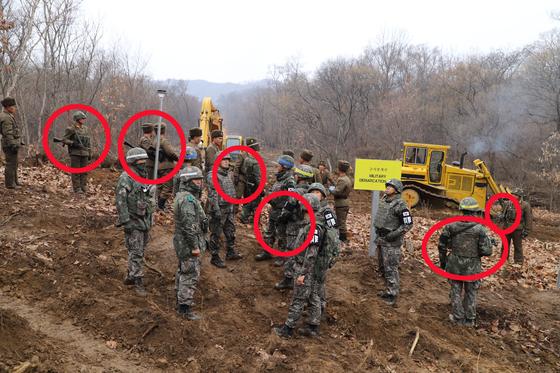남북군사당국이 '판문점선언 이행을 위한 군사분야 합의서'에 따라 공동유해발굴의 원활한 추진을 위해 강원도 철원 '화살머리고지' 일대에서 남북 도로개설을 추진하고 있는 가운데 22일 도로연결 작업에 참여한 남북한 군인들이 군사분계선(MDL) 에서 소총을 메고 대면하고 있다. [사진 국방부]