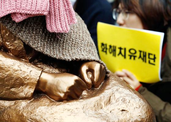 21일 서울 중학동에서 열린 제1362차 정기 수요집회에서 한 참가자가 소녀상 앞에서 피켓을 들고 있다. 정부는 이날 2015년 한일 위안부 합의로 만들어진 화해·치유 재단 해산을 공식 발표했다. [뉴시스]