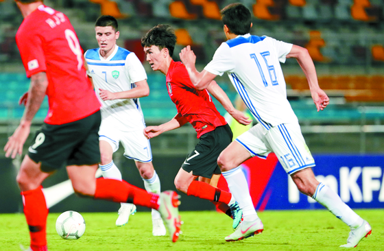 축구대표팀 중앙 미드필더 황인범(가운데)이 20일 우즈베키스탄과의 축구대표팀 평가전에서 드리블을 하고 있다. 황인범은 선배 기성용의 공백을 잘 메우며 팀에 활력을 불어 넣었다는 평가를 받았다. [연합뉴스]