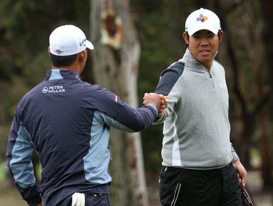 23일 열린 골프 월드컵 2라운드에서 김시우(왼쪽)와 손을 맞추는 안병훈. [EPA=연합뉴스]