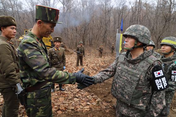 22일 도로연결 작업에 참여한 남북인원들이 군사분계선(MDL) 인근에서 인사하고 있다. [사진 국방부 제공]