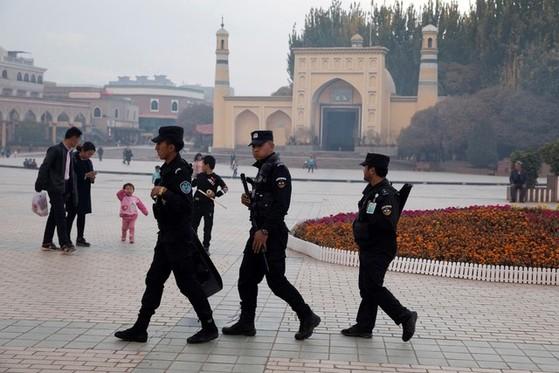 중국 신장 지역 이드 카 모스크 앞 광장을 공안들이 순찰하고 있다. [AP=연합뉴스]