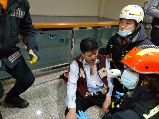 금속노조원들에게 폭행을 당한 유성기업 김모 상무가 119구급대로부터 긴급 치료릅 받고 있다. 김 상무는 지난 22일 유성기업 아산공장 본관 2층 사무실에서 폭행을 당해 병원 치료를 받고 있다. [사진 유성기업]