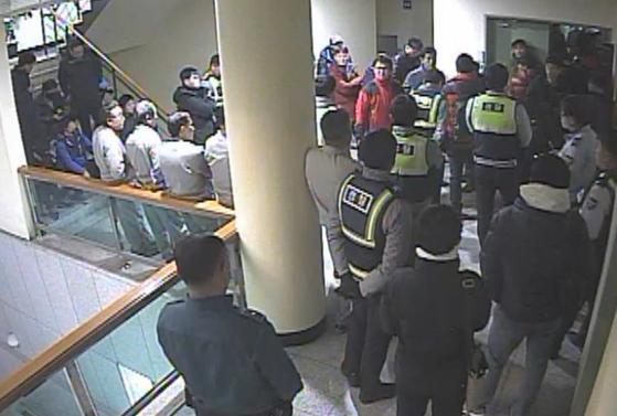 유성기업 금속노조 조합원들이 아산공장 본관 2층 사무실에서 회사 임원을 폭행하고 있다는 신고를 받고 출동한 경찰이 노조원들의 제지에 막혀 사무실로 들어가지 못하고 있다. [사진 유성기업]