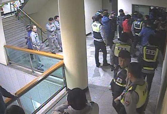 22일 유성기업 금속노조 조합원들이 아산공장 본관 2층 사무실에서 회사 임원을 폭행하고 있다는 신고를 받고 출동한 경찰이 노조원들의 제지에 막혀 사무실로 들어가지 못하고 있다. [사진 유성기업]