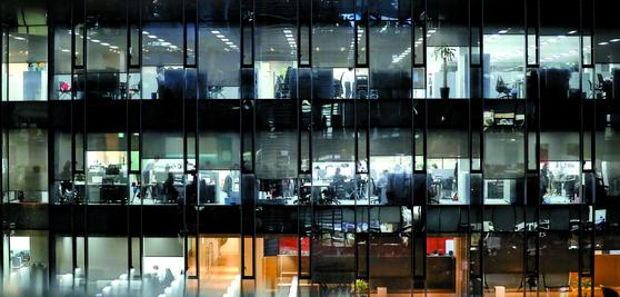 서울의 한 사무실에서 직장인들이 불을 환하게 켜놓고 야근하고 있다. 선택 근로제를 손질해 달라는 IT 업계의 목소리가 커지고 있다. [연합뉴스]