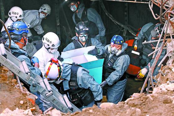 """국과수·경찰·소방당국 등으로 이뤄진 합동조사단이 26일 서울 KT 아현지사 화재 현장에서 채집한 증거물을 상자에 담아 옮기고 있다. 이날 경찰은 '외부요인에 의한 방화 가능성은 작다""""고 밝혔다. [뉴스1]"""