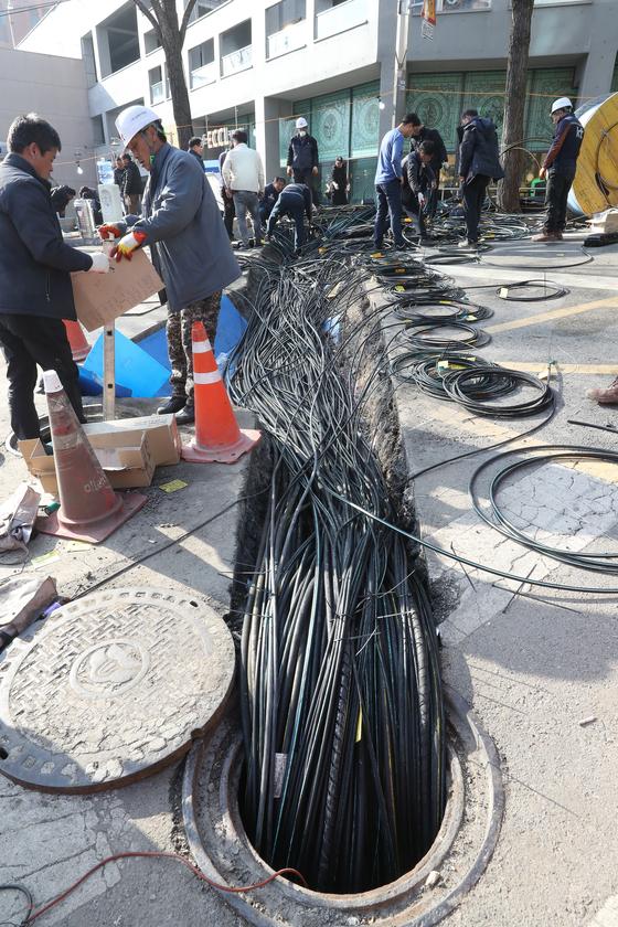 26일 서울 KT아현지사 인근에서 KT관계자들이 통신망 복구를 위해 망을 새로 깔고 있다. [우상조 기자]