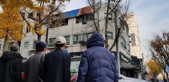 7명이 숨진 서울 국일 고시원 화재 생존자(맨 왼쪽)와 희생자 유가족들이 사고 현장을 떠나지 못하고 있다. 수도권 고시원은 가난해서 갈 곳 없는 '경제 난민'들의 마지막 피난처 같은 곳이다.  장세정 기자