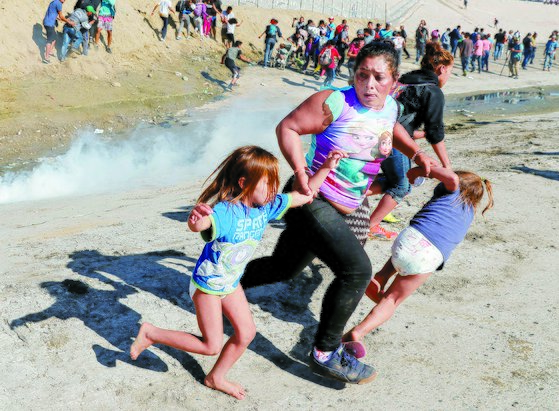 미국 캘리포니아주 샌디에이고와 접경 지역인 멕시코 티후아나에서 25일 미국 쪽으로 국경 진입을 시도하던 온두라스 출신 이주민 모녀가 국경수비대가 발사한 최루탄을 피해 달리고 있다. [로이터=연합뉴스]