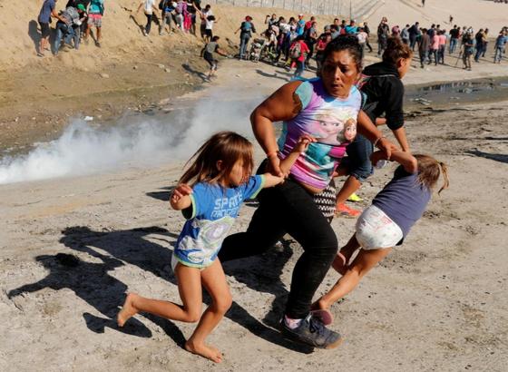 온두라스 출신 이민자 메사와 5살짜리 쌍둥이 두 딸이 멕시코 국경도시 티후아나에서 미국 국경수비대의 최루탄을 피해 달아나고 있다. 한국인 사진기자 김경훈 씨가 찍었다. [로이터=연합뉴스]