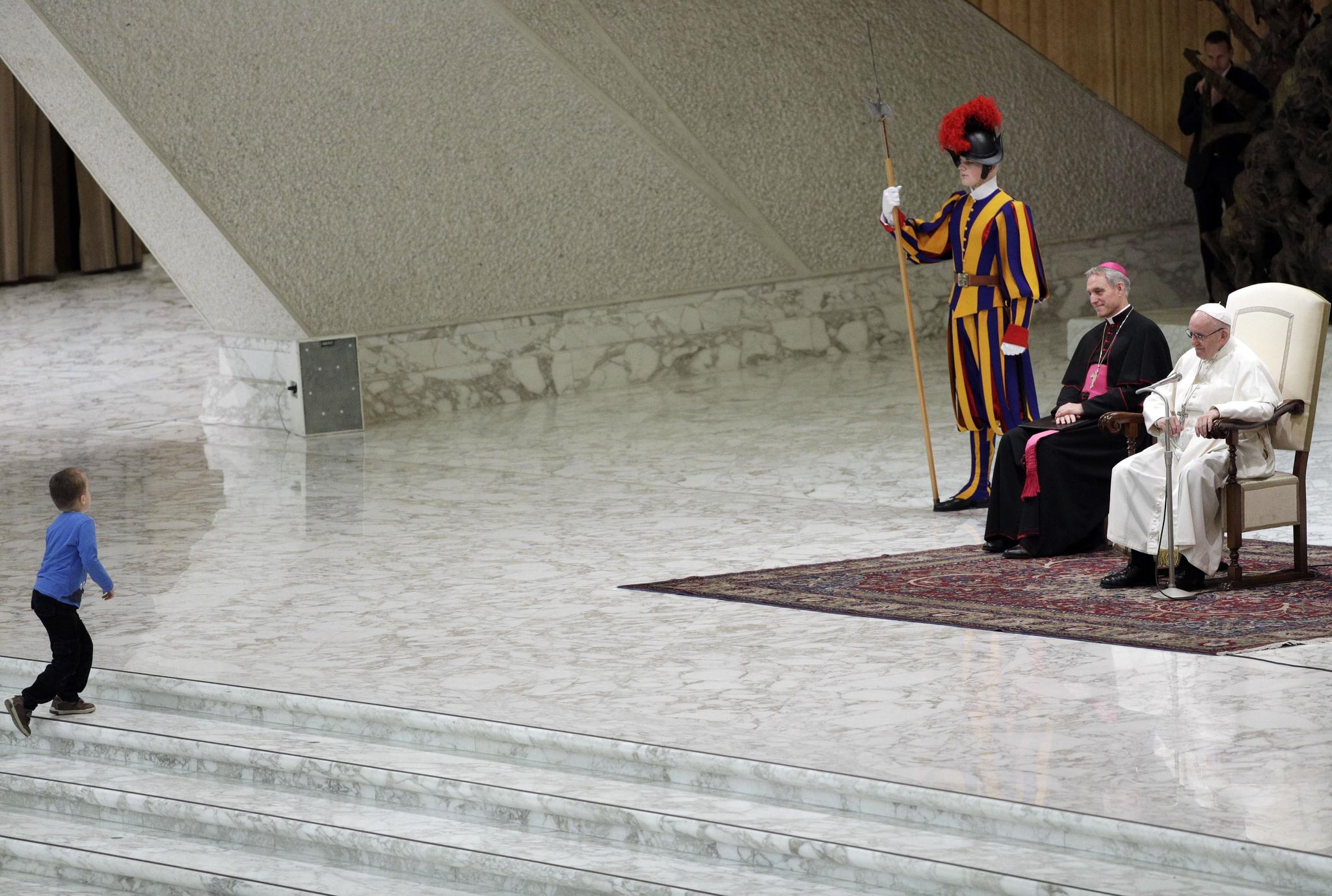 한 아이가 28일(현지시간) 바티칸 바오로 6세 홀에서 열린 수요 일반알현에서 프란치스코 교황이 앉아 있는 단상으로 올라가고 있다. [AP=연합뉴스]