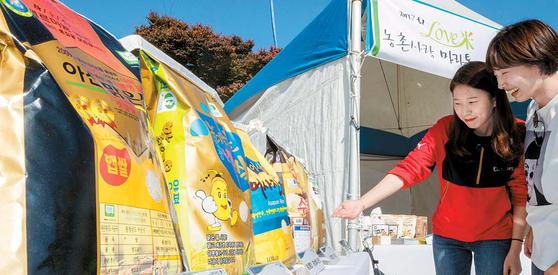 지난달 20일 서울 여의도 한강공원에서 열린 LOVE미 마라톤대회 행사 내 '팔도 농협쌀 대표브랜드 수상 전시회'에서 시민이 브랜드쌀을 보고 있다. [사진 농협]
