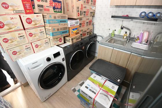 싱크대와 세탁기가 놓여있는 침식칸 내부. 즉석밥과 컵라면 등이 잔뜩 쌓여 있다.