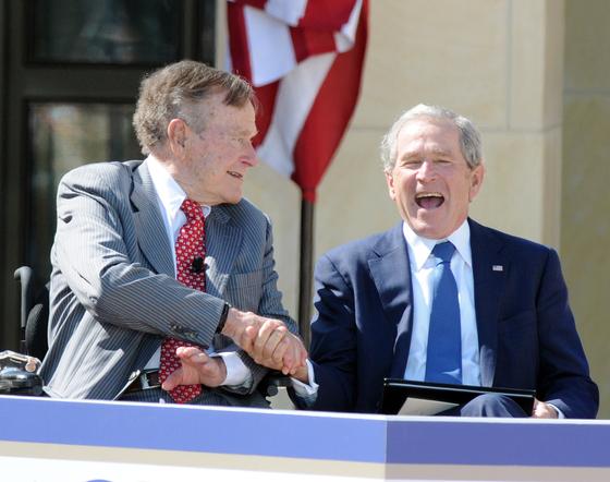 아버지 부시와 아들 부시가 지난 2013년 달라스에 위치한 대통령 기념관에서 손을 맞잡고 웃고 있다. [UPI=연합뉴스]