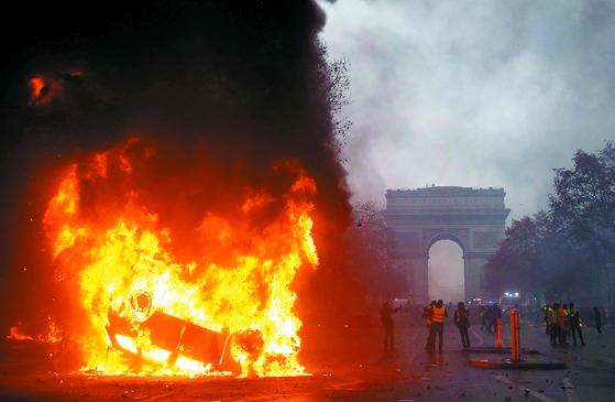 '노란조끼'시위대가 1일(현지시간) 파리의 중심가인 개선문에서 유류세 인상 등 경제정책에 항의하며시위를 벌이고 있다. 프랑스 정부는 친환경 경제 전환을 목표로 지난 1년간 유류세를 경유는 23%, 휘발유는 15%를 인상했다. 폭력사태로 번질 것을 대비해 프랑스 정부는 비상사태 선포를 예고했다. [AFP=연합뉴스]