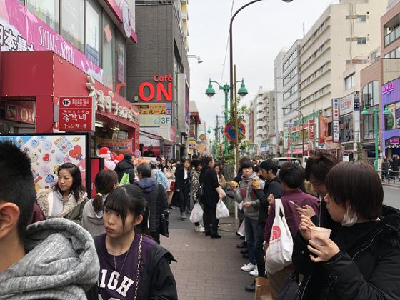 월요일인 3일 신오쿠보역 주변의 거리에서 치즈 핫도그 등 한국 음식을 먹고 있는 손님들의 모습. 서승욱 특파원