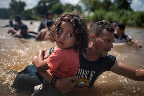 어린아이를 한 팔로 안고 과테말라와 멕시코 국경 사이 강을 건너는 캐러밴 이민자. [로이터-연합뉴스]