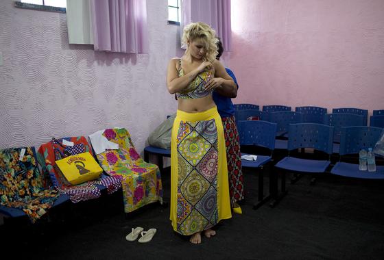 여성 수감자인 Mariana Santos da Silva(23)가 4일(현지시간) 브라질 리우데자네이루에 있는 탈라 베라 브루스 교도소에서 열리는 미인선발대회에 출전하기 전 드레스를 입고 보고 있다. [AP=연합뉴스]