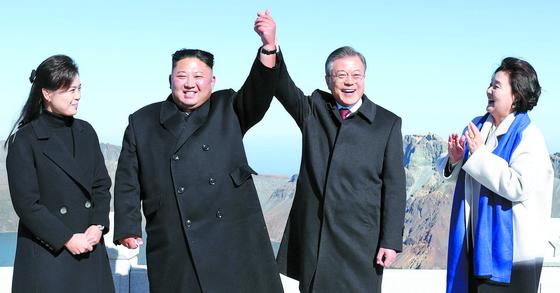 평양정상회담 사흘째인 지난 9월 20일 오전 문재인 대통령과 김정은 국무위원장이 백두산 정상인 장군봉에 올라 손을 맞잡아 들어올리고 있다. [평양=사진공동취재단]