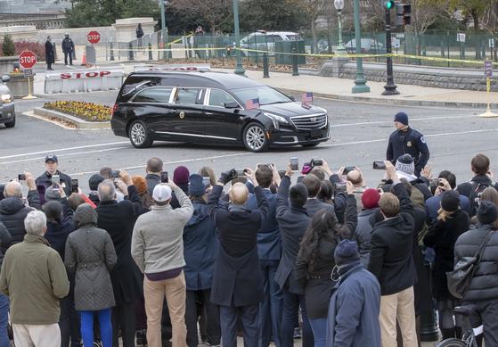 도로에 나온 시민들이 5일 조지 허버트 워커 부지 전 대통령의 리무진 운구차를 촬영하고 있다.[AP=연합뉴스]