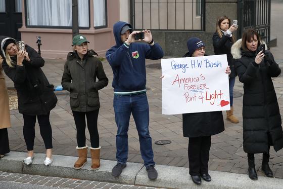 도로에 나온 시민들이 5일 조지 허버트 워커 부지 전 대통령의 리무진 운구차를 향해 피켓들 들고 애도하고 있다.[EPA=연합뉴스]