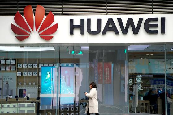 중국 상하이의 화웨이 대리점 앞을 6일(현지시간) 한 여성이 지나고 있다. [로이터=연합뉴스]