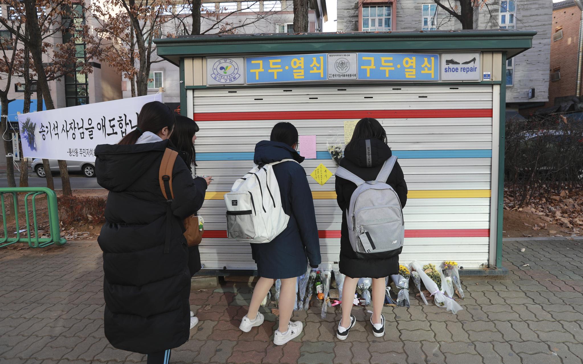 백석역 온수관 파열 사고 희생자 송모(69) 씨가 운영하던 구두수선소 앞에서 학생들이 애도의 글을 붙이고 있다. 임현동 기자