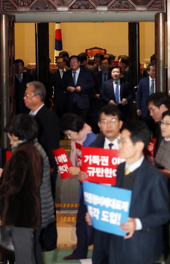 야3당 의원들이 8일 오전 서울 여의도 국회 본회의장 입구에서 농성을 벌이고 있다. 뒤쪽은 본회의를 마친 뒤 빠져나가는 더불어민주당, 자유한국당 의원들. [중앙포토]