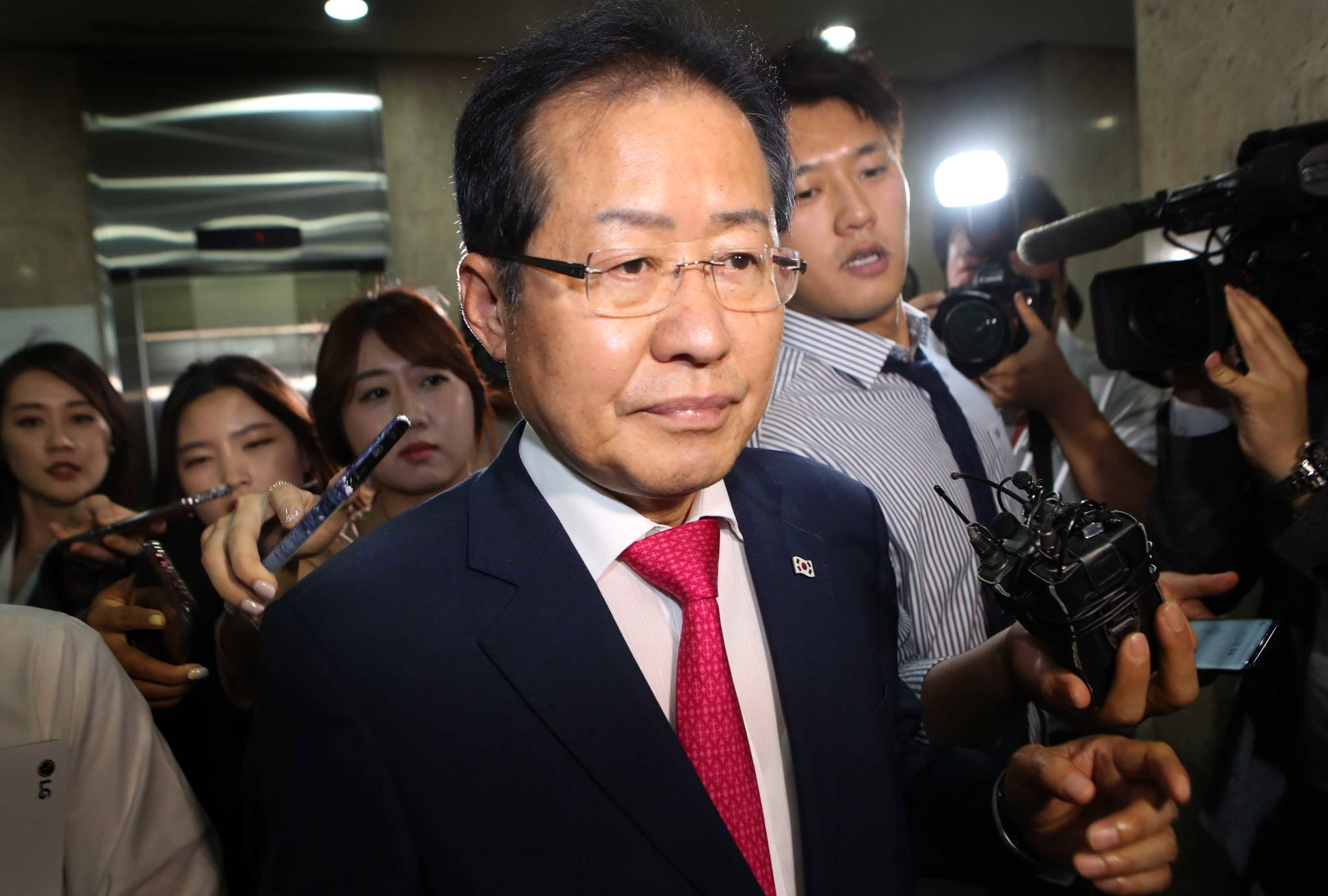자유한국당 홍준표가 14일 지방선거 참패에 책임을 지고 대표직에서 사퇴한 뒤 당사를 나서고 있다.