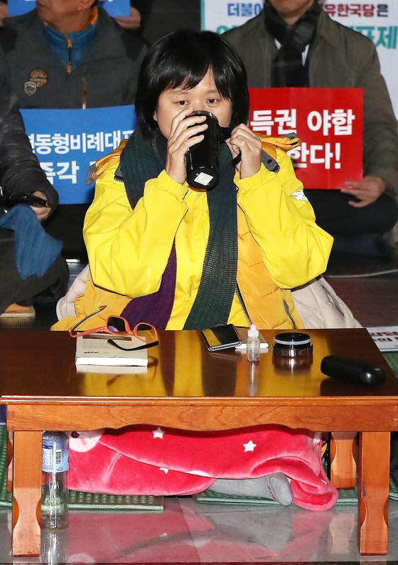 선거제도 개편을 요구하며 단식 농성 중인 정의당 이정미 대표가 9일 서울 여의도 국회 로텐더 홀에서에서 물을 마시고 있다. [뉴스1]