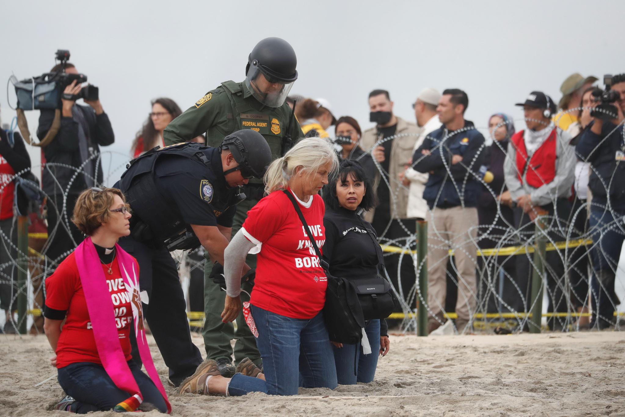 """미국 경찰과 세관국경보호국 (CBP) 요원이 카라반 지지 시위를 벌인 여성들을 체포하고 있다. 시위자들의 셔츠에 """"사랑은 국경이 없다""""(Love Knows No Borders)는 문구가 새겨져 있다. [REUTERS=연합뉴스]"""