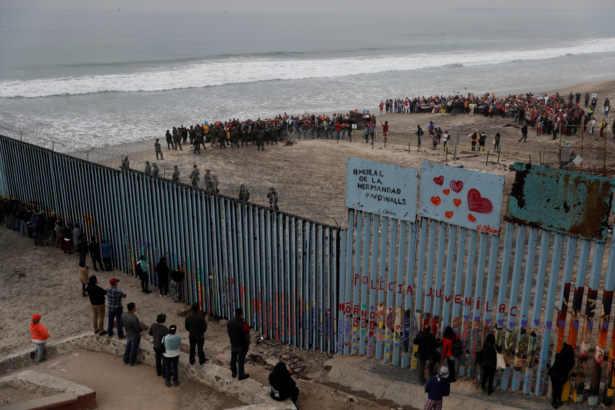 멕시코 티후아나에 가까운 미국 샌디에고 시민들이 10일 중미 이민자 '카라반'을 지지하는 집회를 열고 있다. 멕시코와 미국 국경에 설치된 철제 방벽 위에는 '우애의 방벽'(mural de la hermandad)이라는 스페인어와 '방벽 반대'(No Walls)가 적혀 있다. [로이터=연합뉴스]