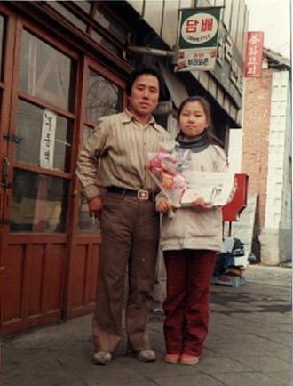 미아동에서 작은 부품가게를 운영하셨던 장인어른은 가족과 동네의 연결 중심이셨다. 1980년대 초반 '태양사' 앞에서 장인어른과 나의 아내. [사진 박헌정]