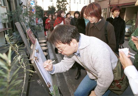 도쿄의 한 식당을 찾은 손님들이 줄 선 순서에 따라 칠판에 이름을 적으며 점심식사 시간을 확인하고 있다. [중앙포토]